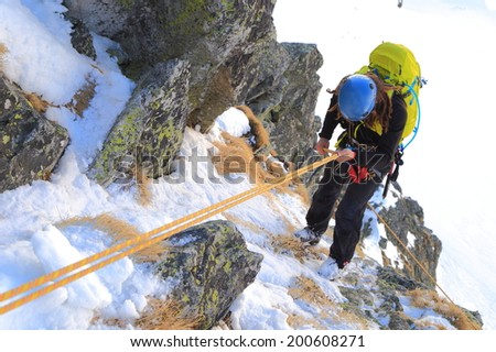 Mountaineer descending snow covered gully by abseil - stock photo