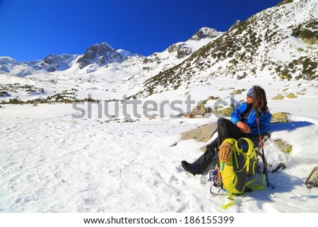 Mountaineer enjoying the sun while resting in winter - stock photo