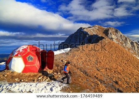 Mountaineer exits dome shaped refuge located near the summit - stock photo