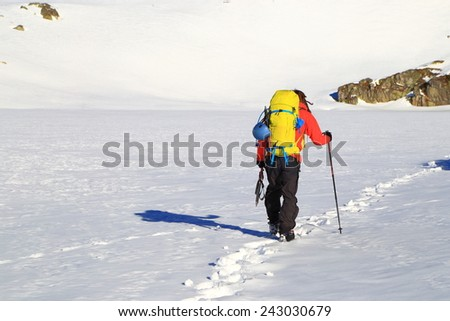 Mountaineer follows a trail of foot steps during winter - stock photo