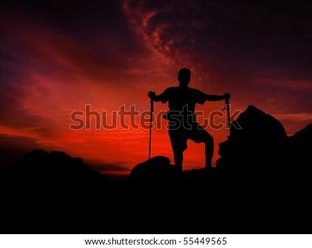 Mountaineer is watching beautiful red sunset on the mountain peak - stock photo