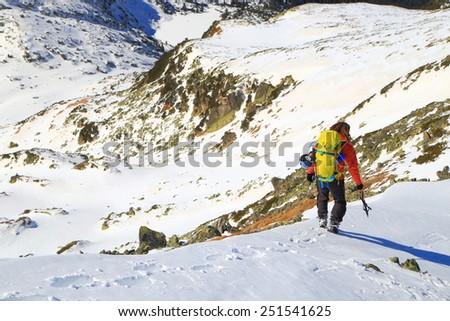 Mountaineer on snowy mountain ridge in fine winter day - stock photo