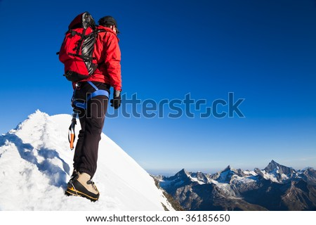 Mountaineer on the snowy ridge of Breithorn,  looking at the peaks around Zermatt with the Weisshorn. Switzerland, Europe.