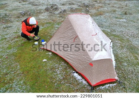 Mountaineer prepared food near the tent - stock photo