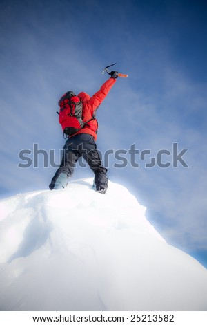 Mountaineer reaches the top of a mountain peak and expresses his joy. Vertical frame. Soft-focus version - stock photo