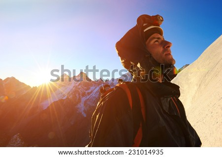 Mountaineer reaches the top of a snowy mountain