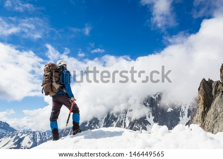 Mountaineer reaches the top of a snowy mountain in a sunny winter day. Alps, Italy. - stock photo