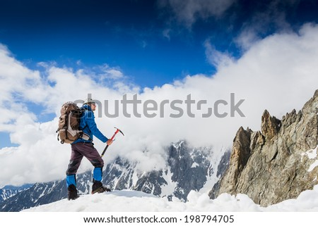 Mountaineer reaches the top of a snowy mountain in a sunny winter day. Alps, Italy.