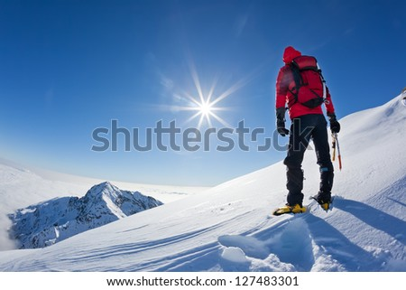 Mountaineer reaches the top of a snowy mountain in a sunny winter day. Western Alps, Biella, Italy.