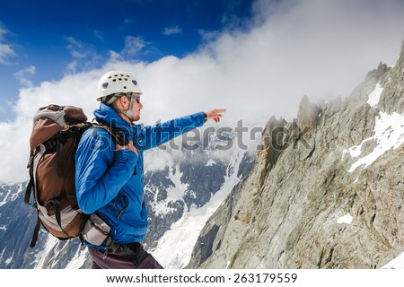 Mountaineer reaches the top of a snowy mountain in Alps  - stock photo