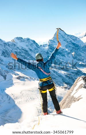 Mountaineer reaches the top of a snowy mountain, Nepal Himalayas - stock photo