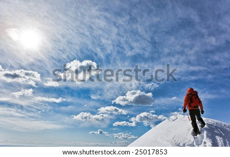 Mountaineer reaching the top of a snowcapped mountain peak (HDR version). Horizontal frame. - stock photo