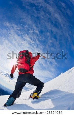 Mountaineer reaching the top of a snowcapped mountain peak (HDR version). Vertical frame.