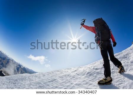 Mountaineer reaching the top of a snowcapped mountain peak,  Mt. Grivola, west italian alps, Europe. Horizontal frame. - stock photo
