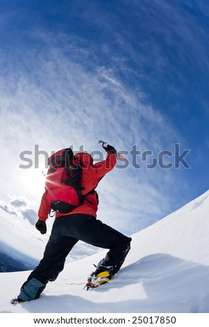 Mountaineer reaching the top of a snowcapped mountain peak. Vertical frame.