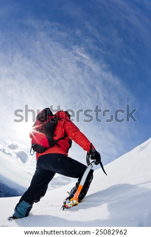 Mountaineer reaching the top of a snowcapped mountain peak. Vertical frame. - stock photo