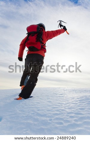 Mountaineer reaching the top of a snowy mountain. Vertical frame.