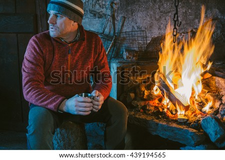 Mountaineer resting in the shelter front of the fire