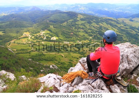 Mountaineer resting on top of the mountain - stock photo
