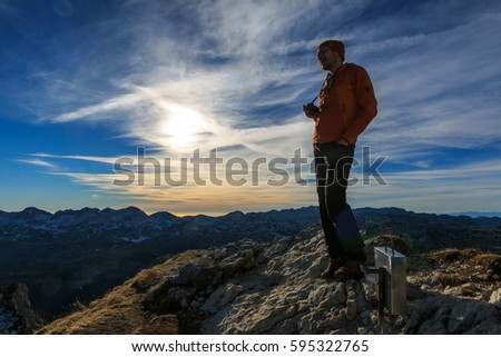 Mountaineer silhouette at the sunset on the top of Ticarica mountain in Triglav national park