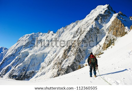 Mountaineer sport. A climber reaching the summit of the mountain - stock photo