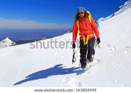 Mountaineer traversing on snow covered slope in sunny winter day - stock photo