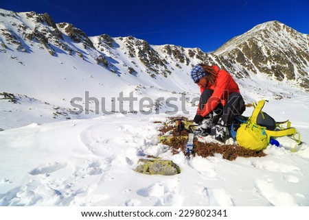 Mountaineer unties the crampons while sitting on the snow - stock photo
