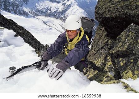 Mountaineer using an ice axe to climb a steep slope - stock photo