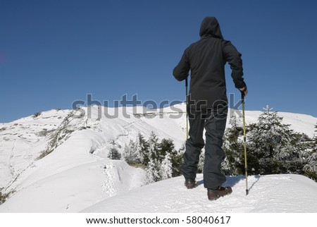 Mountaineer walking on snow mountain under blue sky.