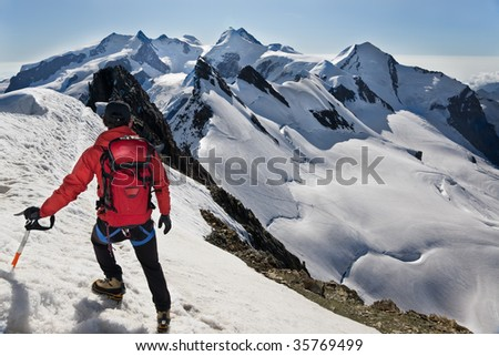 Mountaineer walks down along the snowy ridge of Breithorn, exactly on the swiss-italian border. IIn background the main peaks of Monte Rosa massif Switzerland, Europe.