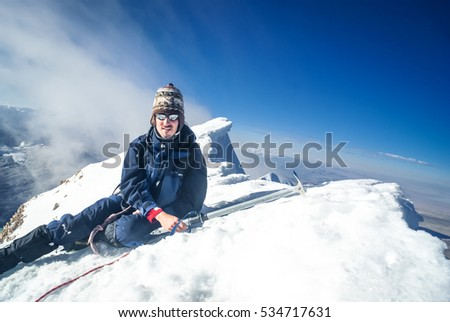 Mountaineer with sunglasses and knitted cap sitting and posing to photocamera at snowy top of Huayna Potosi, mountain in Bolivia, South America.