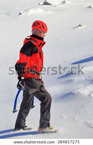 Mountaineer woman carrying ice axes on snowy trail - stock photo