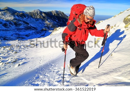 Mountaineer woman climbs a snowy trail with a red backpack  - stock photo