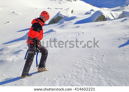 Mountaineer woman climbs in sunny winter day in Retezat mountains, Romania