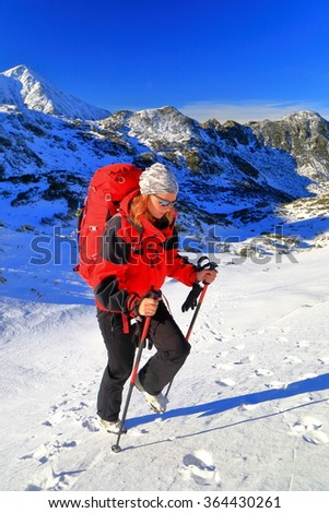 Mountaineer woman climbs with a red backpack on snow covered trail to the summit, Retezat massif, Romania - stock photo