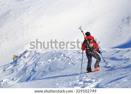 Mountaineer woman descending a snowy trail with skis on the backpack - stock photo