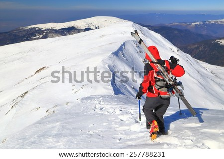 Mountaineer woman traversing a snowy ridge while  carries skies on the backpack