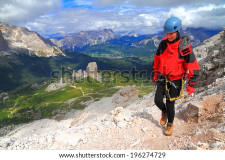 Mountaineer woman walking a trail to Averau summit, Dolomite Alps, Italy