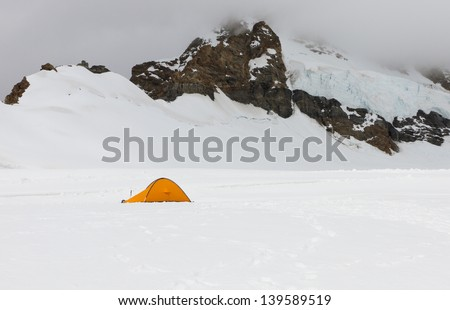 mountaineering, adventure, expedition concept: tent in high altitude alps with snow and glacier, Switzerland - stock photo