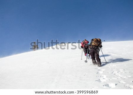 mountaineering group of tourists climbing up the snow covered mountain. The steep slope and a snowstorm on a clear day - stock photo