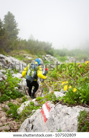 Mountaineering in the Alps - hikers walking down a hiking trail covered by clouds - stock photo