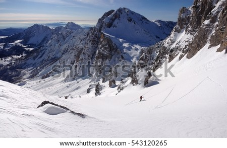 Mountaineering skier while climbing on the hill, panoramic view of snowy mountain, geometric ski tracks on snow, Dolomites, Italy