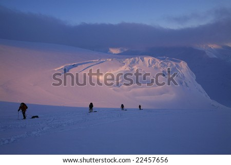 Mountaineering team ascending the upper Kahiltna Glacier to 11,200 camp, at around midnight, on Denali, Denali National Park, Alaska. - stock photo