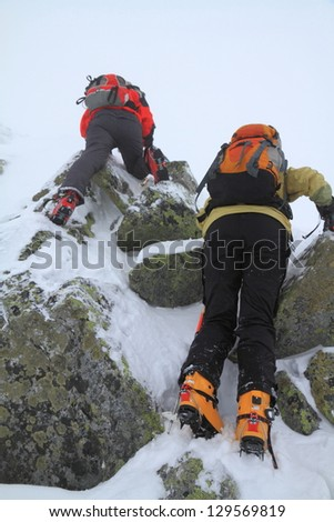 Mountaineers climbing a steep rocky route in bad weather during winter - stock photo
