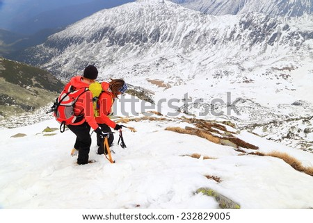Mountaineers descending a steep snow covered mountain with care - stock photo