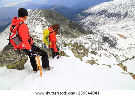 Mountaineers descending carefully on snow covered mountain slope - stock photo