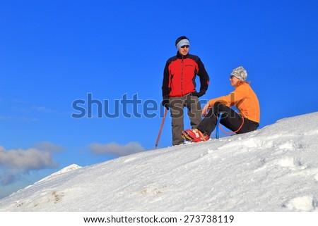 Mountaineers enjoying fine weather on snow covered peak  - stock photo