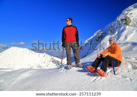 Mountaineers relaxing on snowy area of the mountain in winter - stock photo
