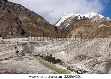 Mountaineers Walking Across Large Glacier Group of Mountain Climbers Crossing Ice Section along Water Stream Flowing on Glacier Surface During Ascent of Alpine Expedition in Asia Mountain Area - stock photo
