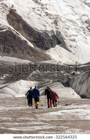 Mountaineers Walking Across Large Glacier Group of Mountain Climbers with High Altitude Boots and Clothing Crossing Ice Section During Ascent of Alpine Expedition in Asia Mountain Area Vertical - stock photo